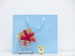 cool shopping bag, gift in shopping cart and alarm clock on the wonderful white background