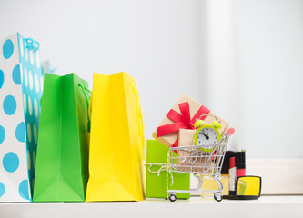 cute shopping bags, make up set, gifts and alarm clock in shopping cart on the wonderful mirror background