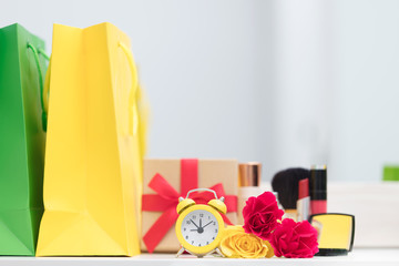 cute shopping bags, make up set, gift, alarm clock and roses on the wonderful mirror background