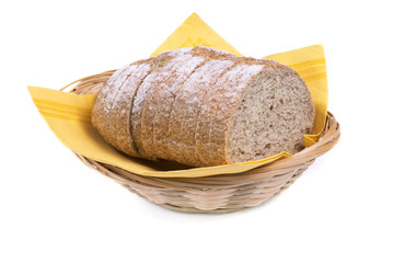 pain complet en tranche dans panier tressé sur fond blanc
