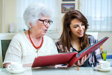 Grandma and her granddaughter looking at photo album together at home.