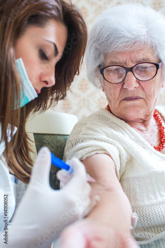 Nurse Prepares To Give Senior Patient An Injection Stock
