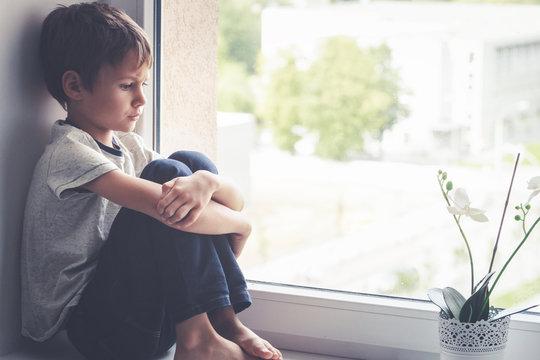 Sad child sitting on window shield.