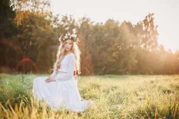 Charming bride in a field alone. The bride in the rays of the evening sun.