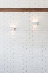 White brick wall with two lights and wooden beam
