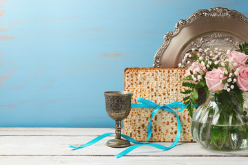 Jewish holiday Passover Pesah background with matzoh, rose flowers and wine glass on wooden table with copy space