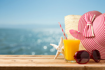 Summer holiday vacation concept with orange juice, hat and sunglasses over sea beach background