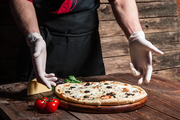 Culinary master class. Italian cuisine. Cooking and decorating delicious pizza from professional chef.