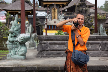 male traveler photographer takes pictures in the territory of a Buddhist temple in island Bali. Indonesia