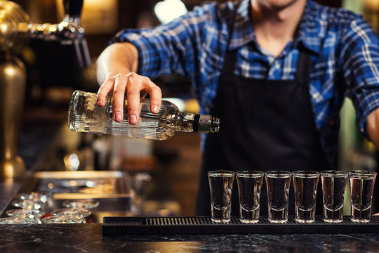 Barman at work,Barman pouring hard spirit into glasses in detail,Bartender is pouring tequila into glass,preparing cocktails,concept about service and beverages