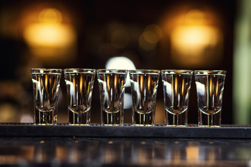 Barman at work,Barman pouring hard spirit into glasses in detail,Alcoholic shots of tequila or strong drink in small glasses, with lime garnish ready to be served,concept about service and beverages