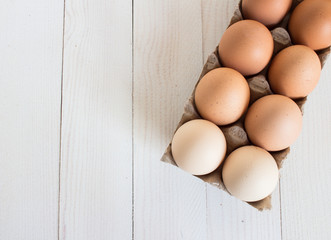 Fresh eggs in carton package on white wood background