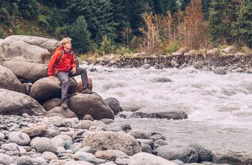 Man traveler sits on mountain river bank