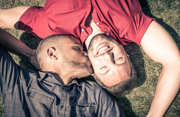Happy gay couple lying down on the grass