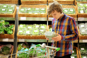 Young man buying vegetables at the market   .Young man in the supermarket .