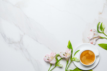Morning romantic breakfast. Coffee and flowers on marble background. Top view