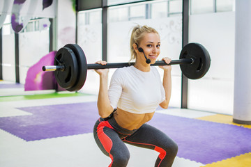 Sporty girl with microphone doing some squats with a barbell in a gym.