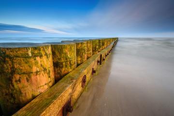 A breakwater on a sandy beach in Leba, Poland, Europe. Baltic sea.