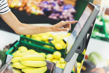 buyer weighs yellow bananas and points fingers on the screen electronic scales, woman shopping healthy food in supermarket blur background, hands buy nature products in store grocery