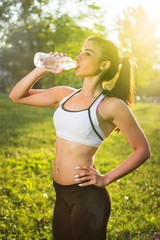 Young smiling woman drinking water from bottle after fitness sport exercise outdoors at sunset.