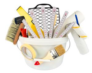 paint bucket filled with handyman renovation tools paint and equipment isolated on white background / Werkzeug Set ausrüstung zur renovierung anstreichen tapezieren isoliert auf weiß