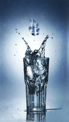 Splashing water of ice in a cool glass of water