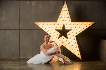 Ballerina in tutu and pointe shoes sitting on the floor in studio with alight star on the background