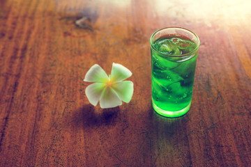 Green water and plumeria flower on wooden table