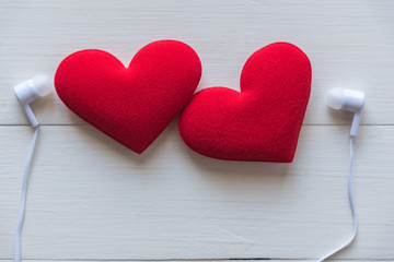 couple red heart with earphone on wooden background