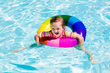 Little girl with toy ring in swimming pool