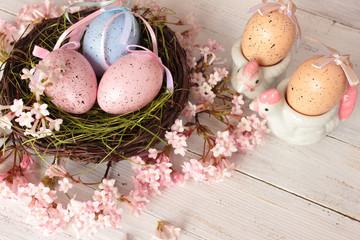 Ostereier im Nest, Huhn als Eierbecher, rosa Blütendekoration auf weißem Holz, Vintage