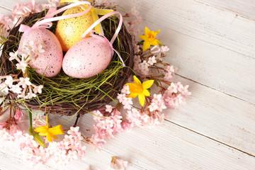 Ostereier im Nest, rosa Blütendekoration mit Narzissen auf weißem Holz, Vintage