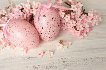 Ostereier und rosa Blütendekoration auf weißem Holz, Vintage