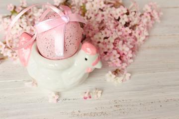 Ostern, Huhn als Eierbecher mit Osterei und rosa Blütendekoration auf weißem Holz, Vintage