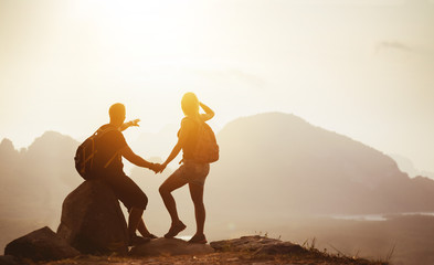 Couple backpackers on mountain top at sunset