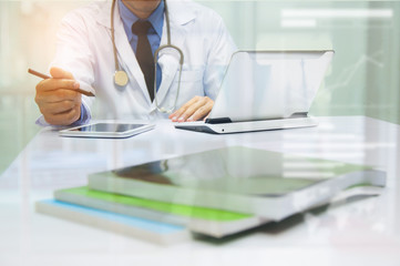 Medicine doctor working with computer notebook and digital tablet at desk in the hospital