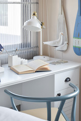 white table with wooden chair books and lamp in modern working area at home