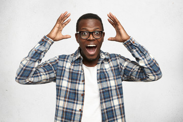 I can't believe this. Amazed young African American hipster wearing trendy glasses and checkered shirt over white t-shirt holding hands in surprised gesture, keeping mouth wide open, looking shocked