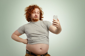 Funny overweight plump man with duck lips wearing undersize t-shirt with belly hanging out of pants, keeping hand on waist, posing for selfie, holding cell phone, trying to seem attractive and sexy