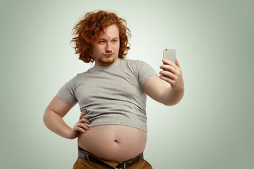 Funny overweight man with fat tummy hanging out of grey t-shirt, standing at studio wall, keeping hand on waist while posing for picture, taking selfie on mobile phone, trying to look seductive