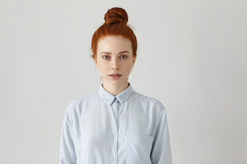 Indoor shot of attractive redhead young female office worker with hair bun posing at studio wall with copy space for your promotional content. Pretty girl dressed in formal shirt having rest indoors