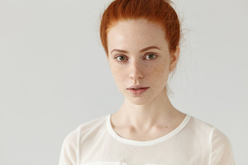 Close up portrait of beautiful young Caucasian woman with healthy freckled skin and ginger hair in bun standing isolated against white studio wall background with copy space for your content