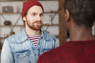 Happy to see you. Portrait of cheerful young bearded Caucasian hipster wearing trendy hat and denim jacket looking at his unrecognizable African friend, listening to him with interest and attention