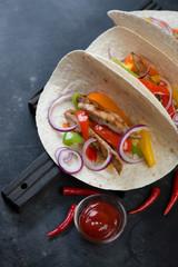 Tortilla bread filled with tex-mex pork fajitas, selective focus, studio shot