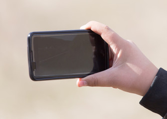The hand with the phone shoots video
