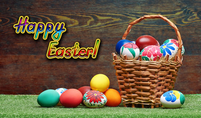 Wicker basket with Easter eggs on a wooden background