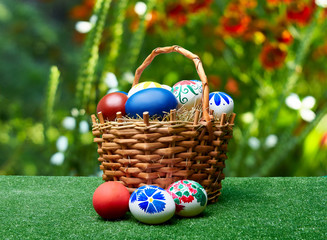 Wicker basket with Easter eggs against the background of summer flowers