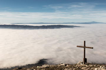 A wooden cross on top of a mountain, with a sea of fog below
