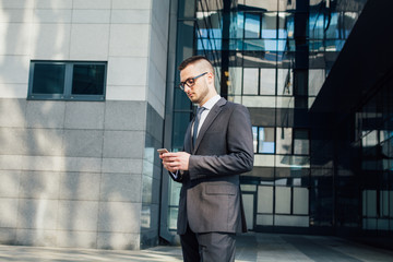 Young businessman standing in front of office by day and using smart phone