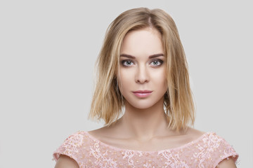 portrait of beautiful blond woman with short hair in pink cocktail dress on grey background